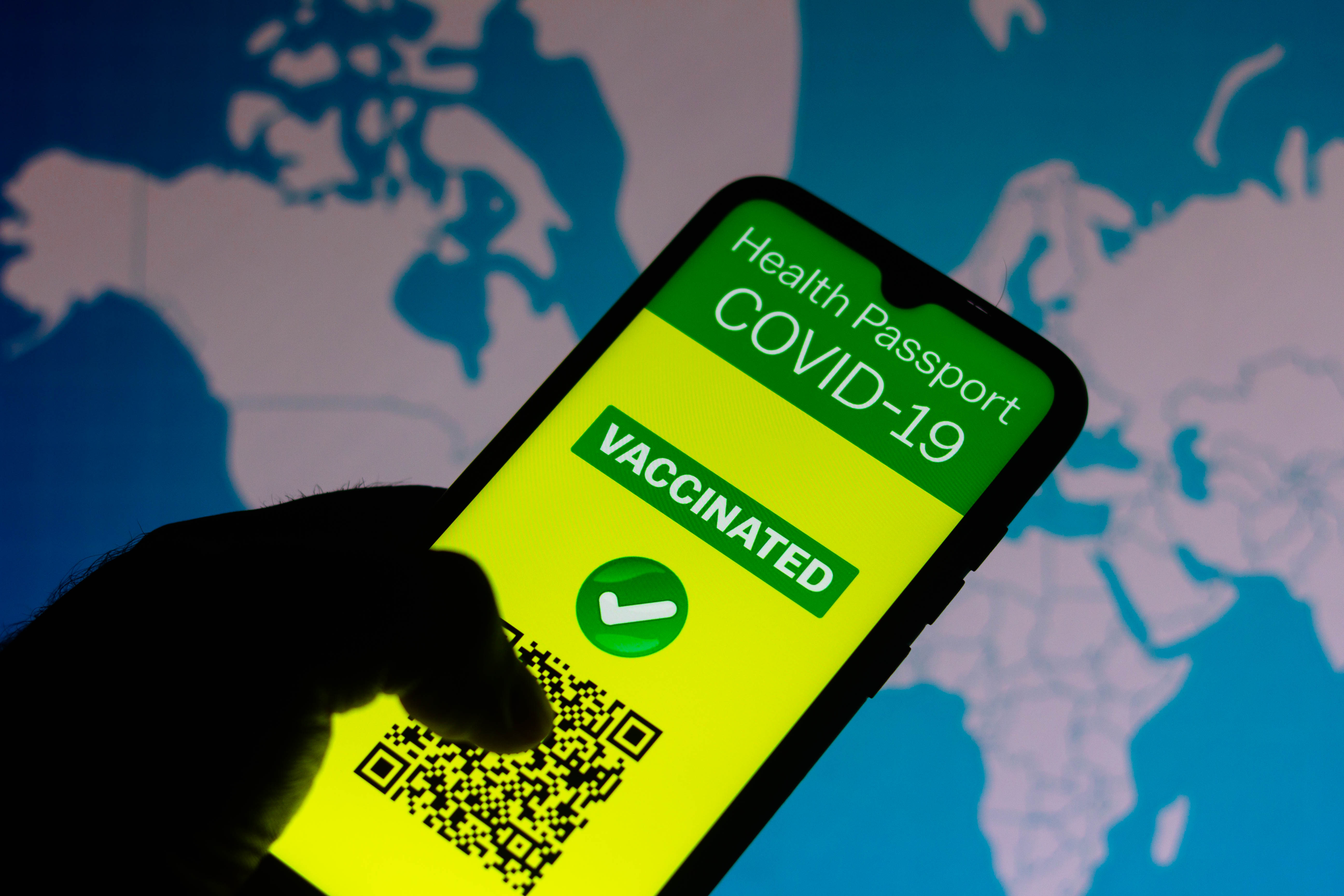 In this photo illustration the vaccination passport application for COVID-19 displayed on the smartphone screen. In the background, a map with coronavirus cases in the world. (Photo by Rafael Henrique / SOPA Images/Sipa USA)No Use Germany.