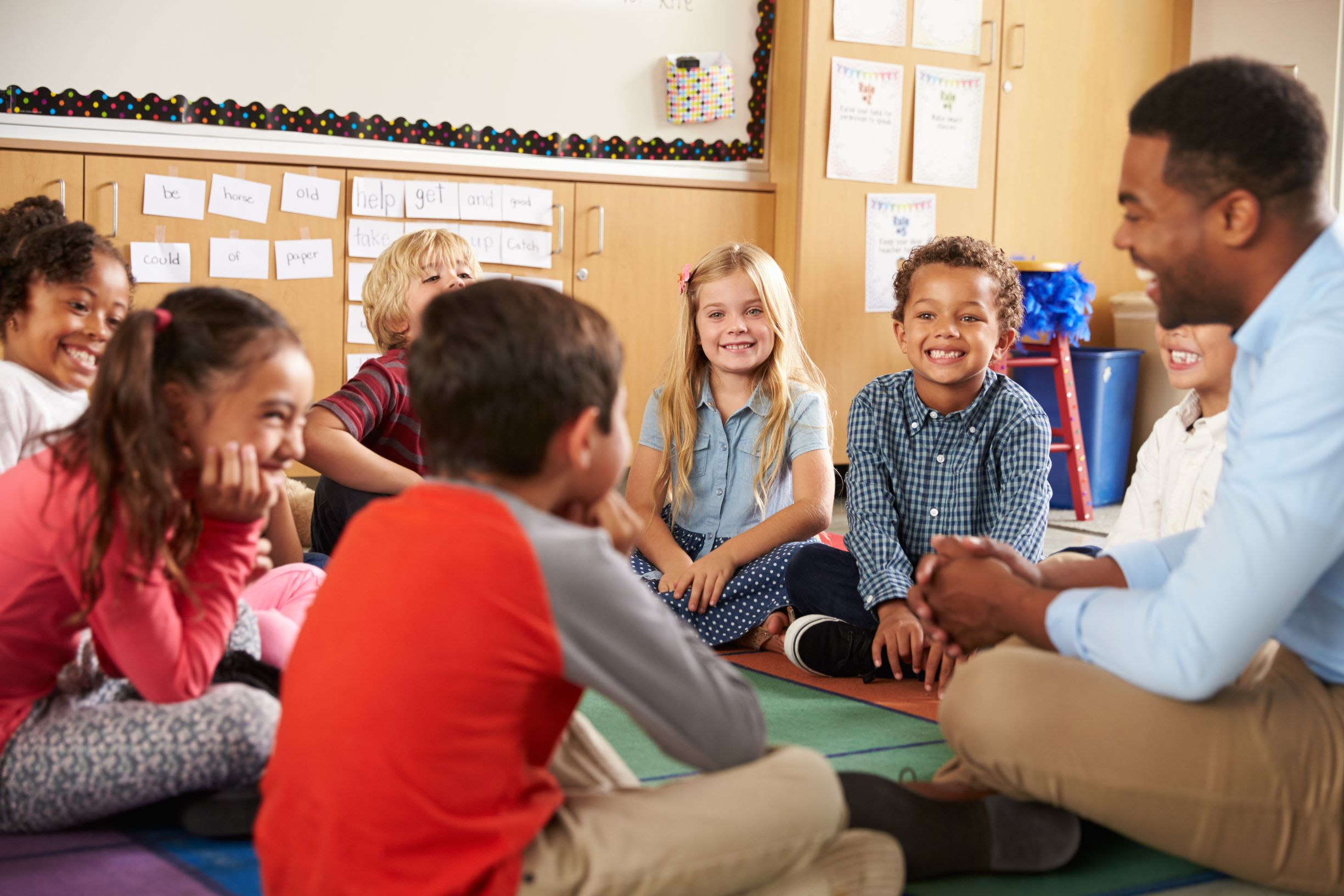 Children sit cross-legged learning together in a classroom.