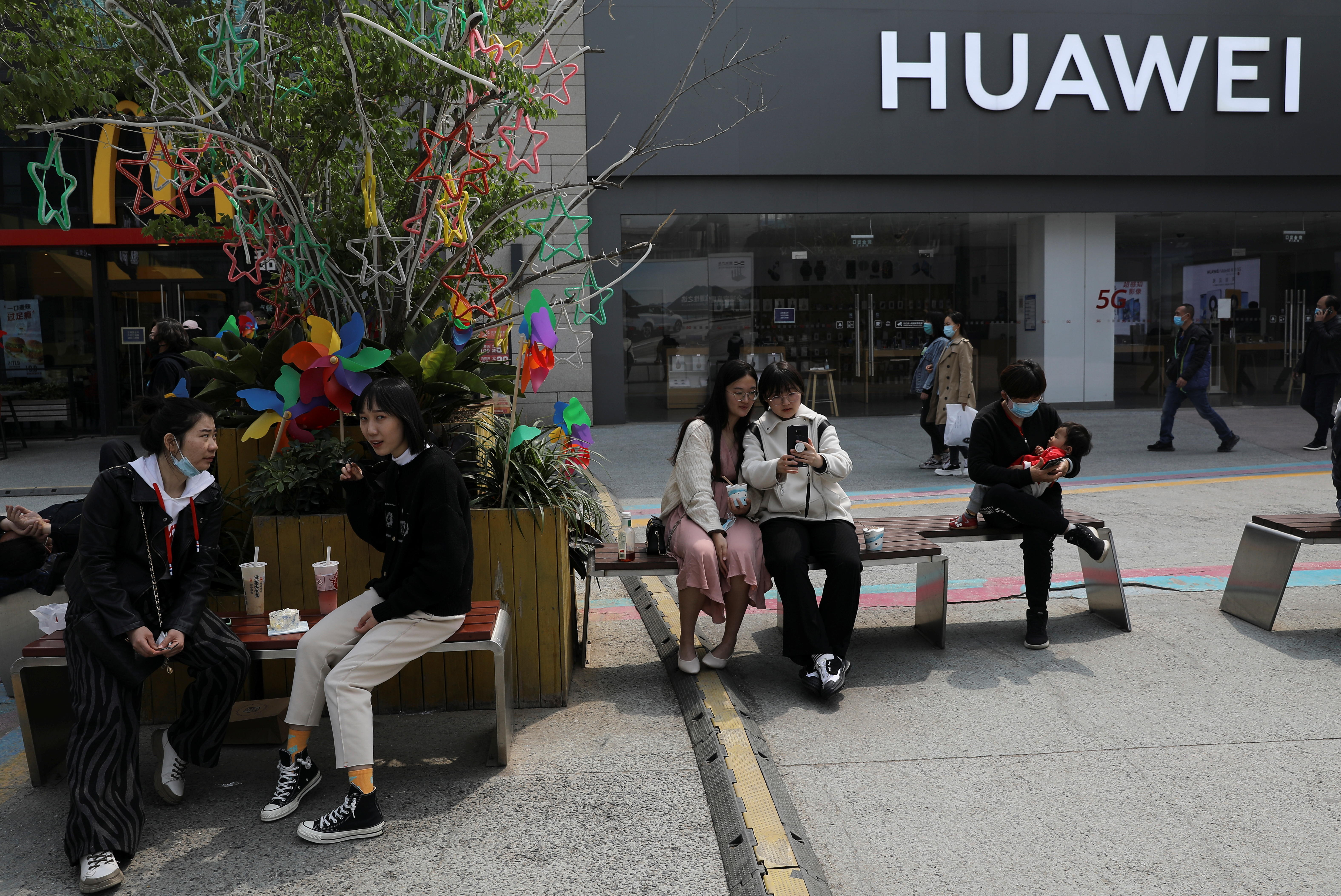 People rest in front of a Huawei store at a shopping complex in Beijing, China April 15, 2021. Picture taken April 15, 2021. REUTERS/Tingshu Wang