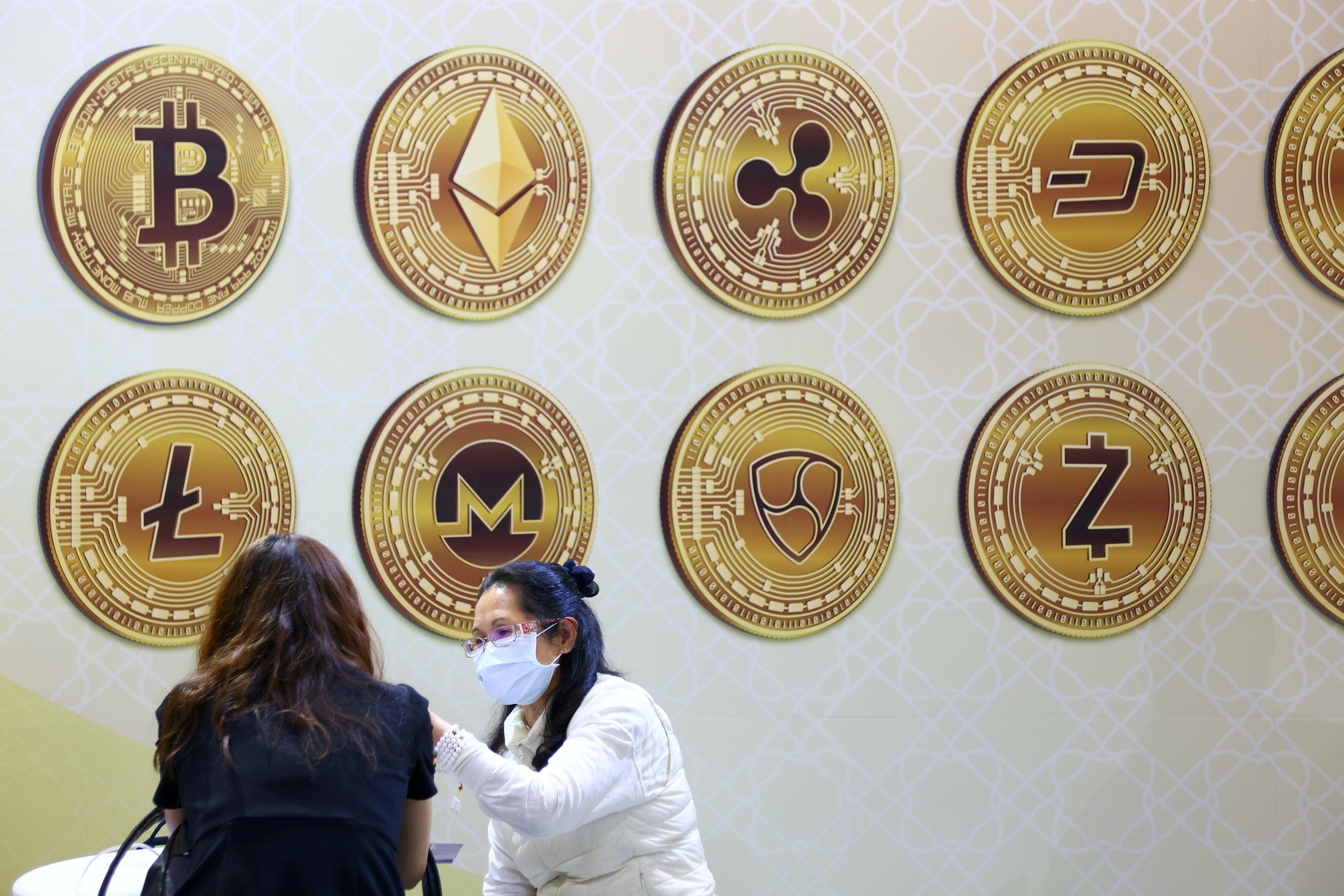 FILE PHOTO: Customers talk against a backboard with signs of cryptocurrency during 2020 Taipei International Finance Expo in Taipei, Taiwan, November 27, 2020. REUTERS/Ann Wang/File Photo