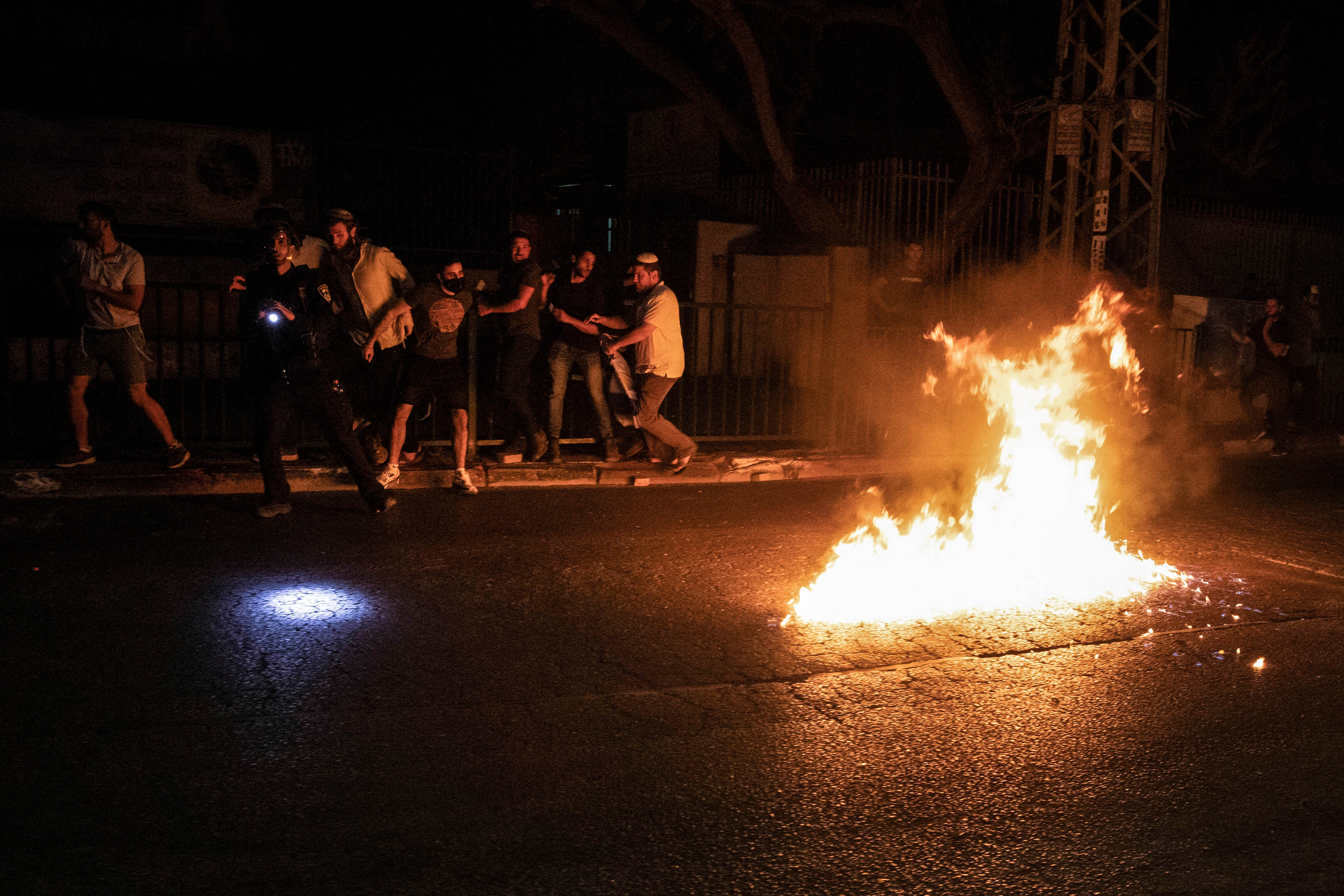 Molotov cocktails are thrown by Arabs at Jewish right-wing protesters during clashes amid a night-time curfew in the mixed Israeli-Arab city of Lod.