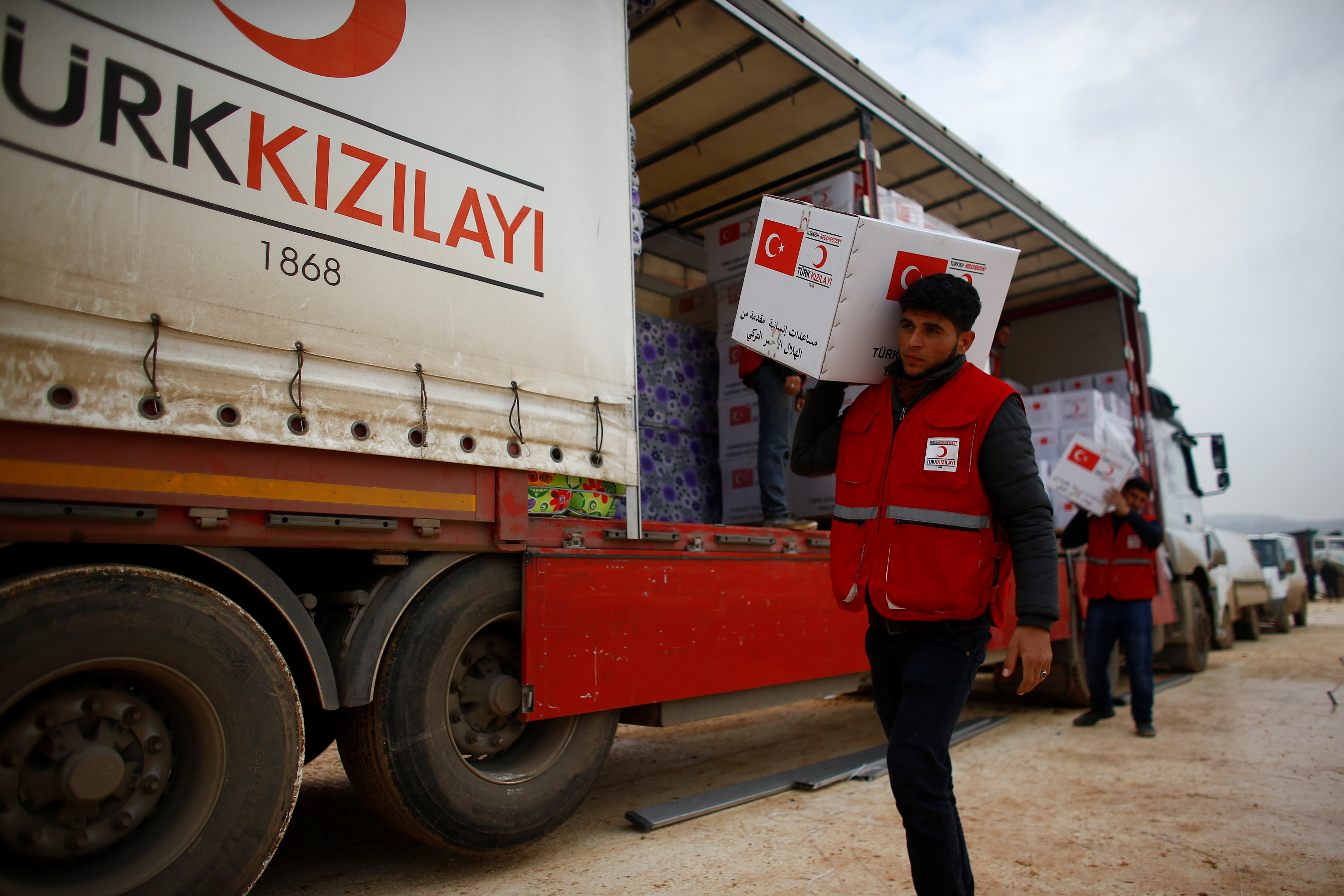 Turkish Red Crescent workers carry humanitarian aid at Kelbit camp, near the Syrian-Turkish border, in Idlib province, Syria January 17, 2018. Picture taken January 17, 2018. REUTERS/Osman Orsal