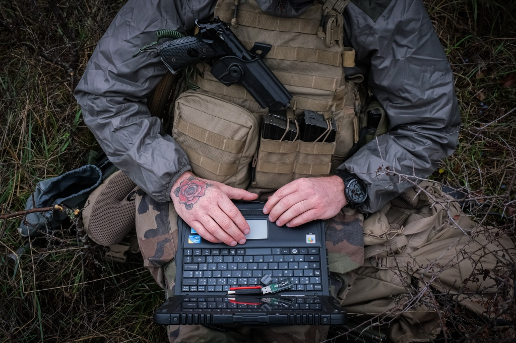 A French soldier is seen operating a laptop computer while seated.
