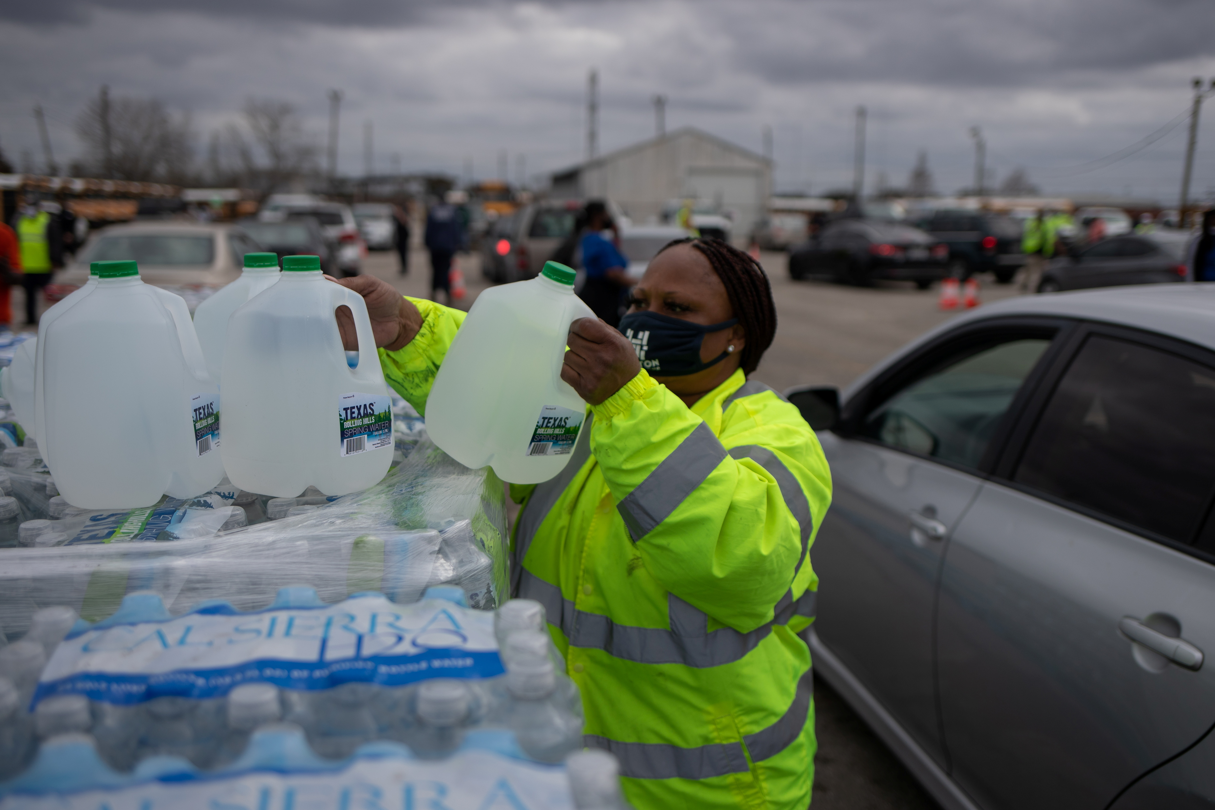 Volunteer Elizabeth Murray helps hand water to local residents at Butler Stadium after the city of Houston implemented a boil water advisory following an unprecedented winter storm in Houston, Texas, U.S., February 21, 2021. REUTERS/Adrees Latif
