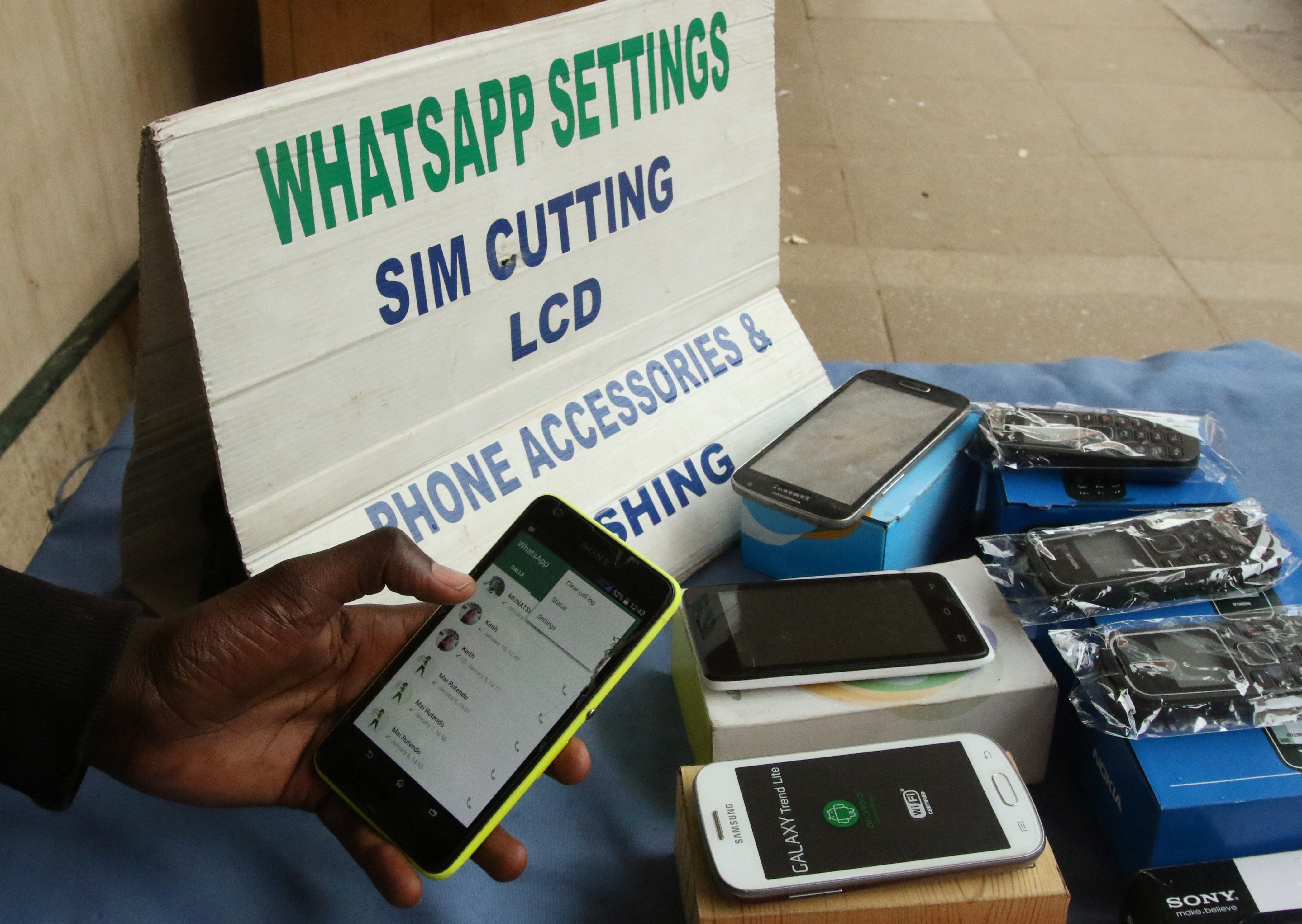 A street vendor adjusts the internet settings on a customer's mobile phone in Harare, Zimbabwe, January 13, 2017. REUTERS/Philimon Bulawayo