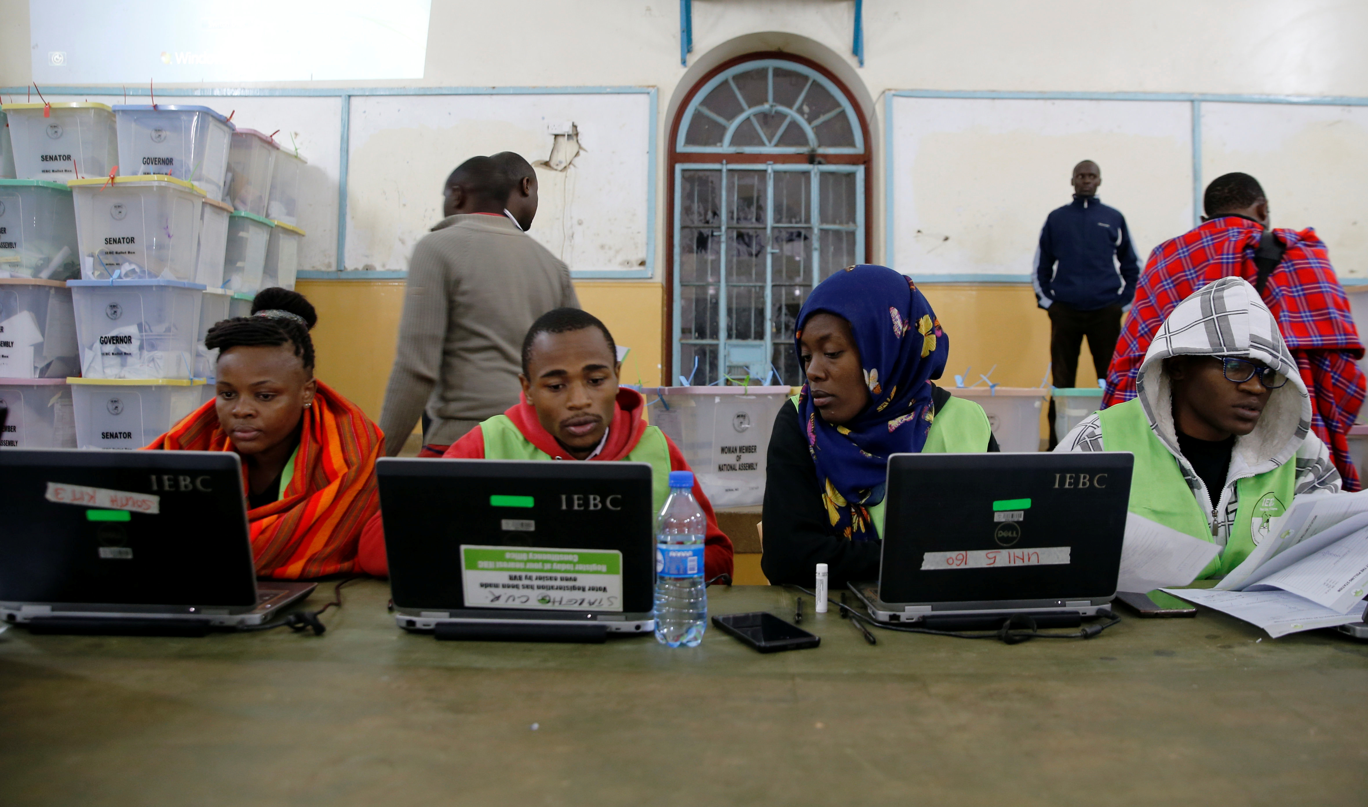 Election officials from the Independent Electoral and Boundaries Commission (IEBC) work on computers in the Jamuhuri High School tallying center in Nairobi, Kenya August 9, 2017. REUTERS/Thomas Mukoya