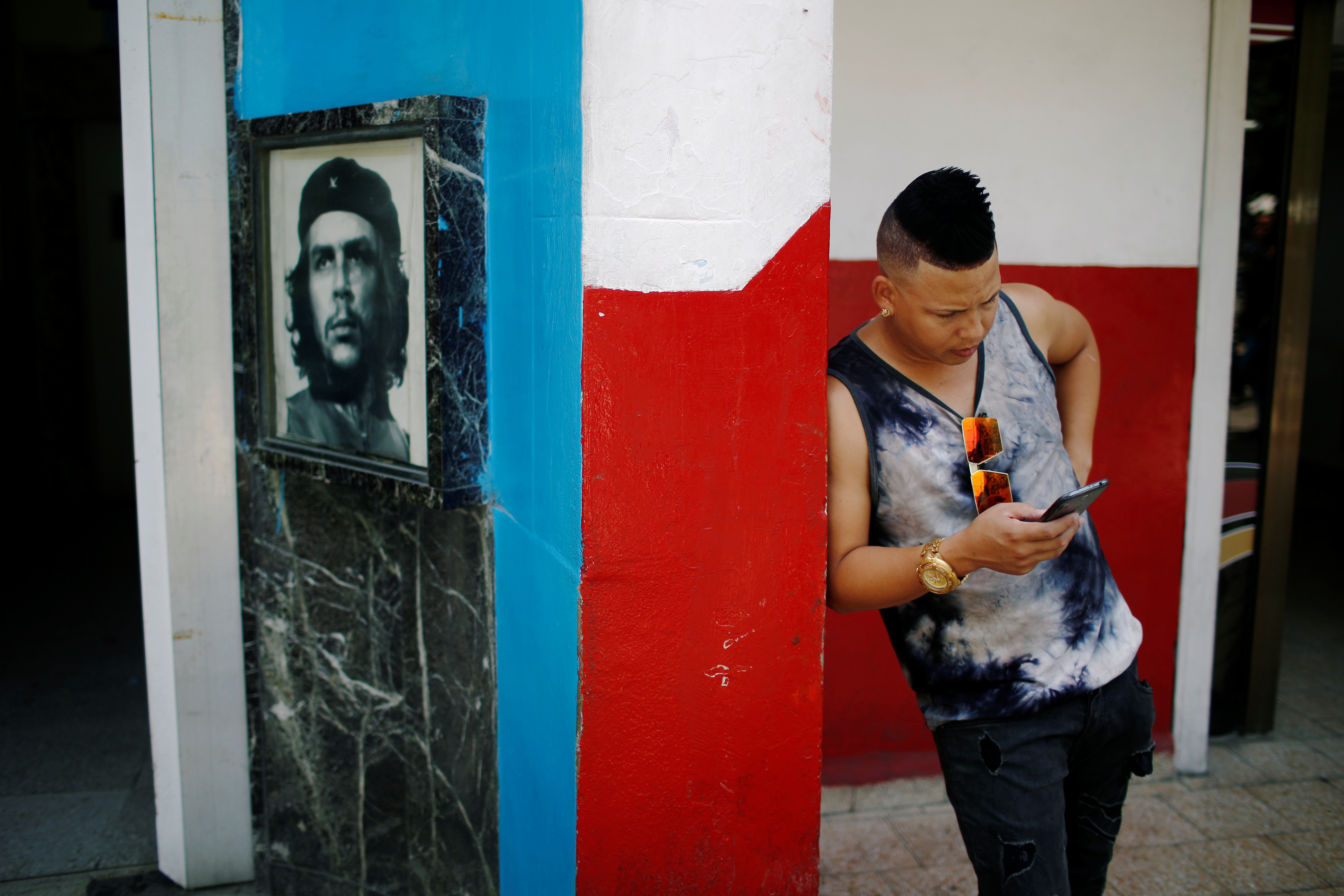 """A young Cuban checks his phone at an internet hotspot next to a picture of late revolutionary hero Ernesto """"Che"""" Guevara in Havana, Cuba August 10, 2018. Picture taken August 10, 2018. REUTERS/Tomas Bravo"""