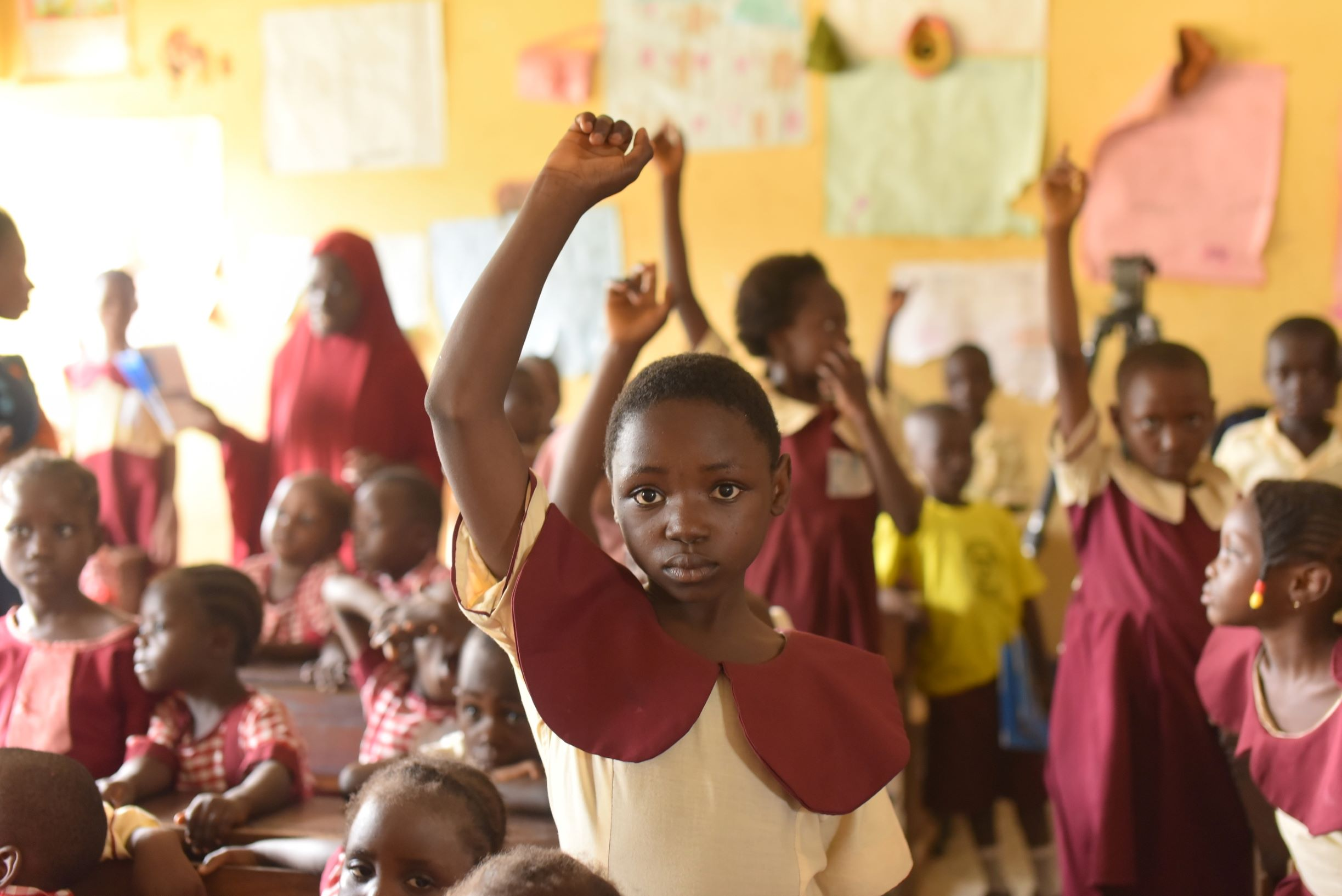 A student in a Nigerian classroom raises her hand.