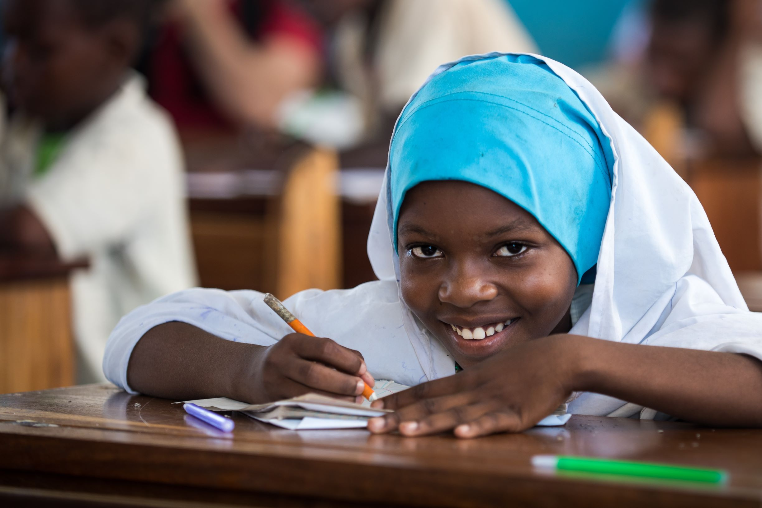 A girl in a classroom in Tanzania smiles at the camera.