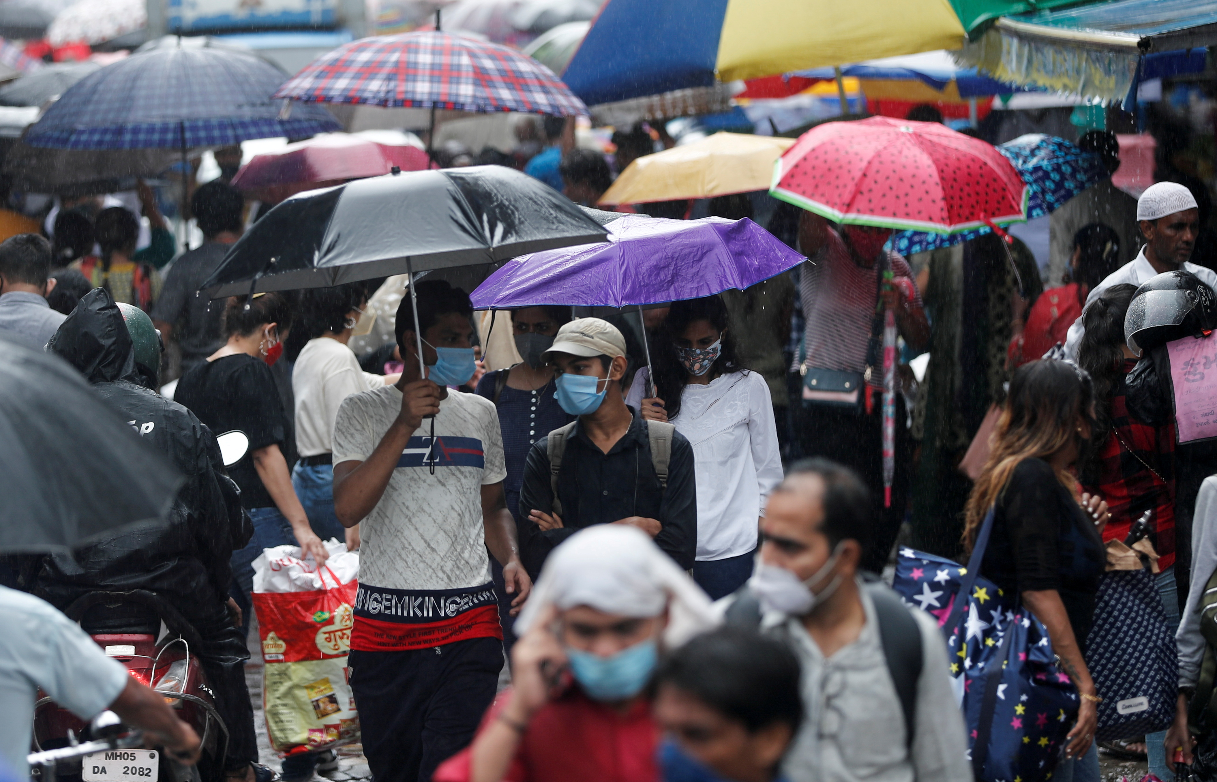 FILE PHOTO: People walk through a crowded market on a rainy day amidst the spread of the coronavirus disease (COVID-19) in Mumbai, India, July 14, 2021. REUTERS/Francis Mascarenhas/File Photo