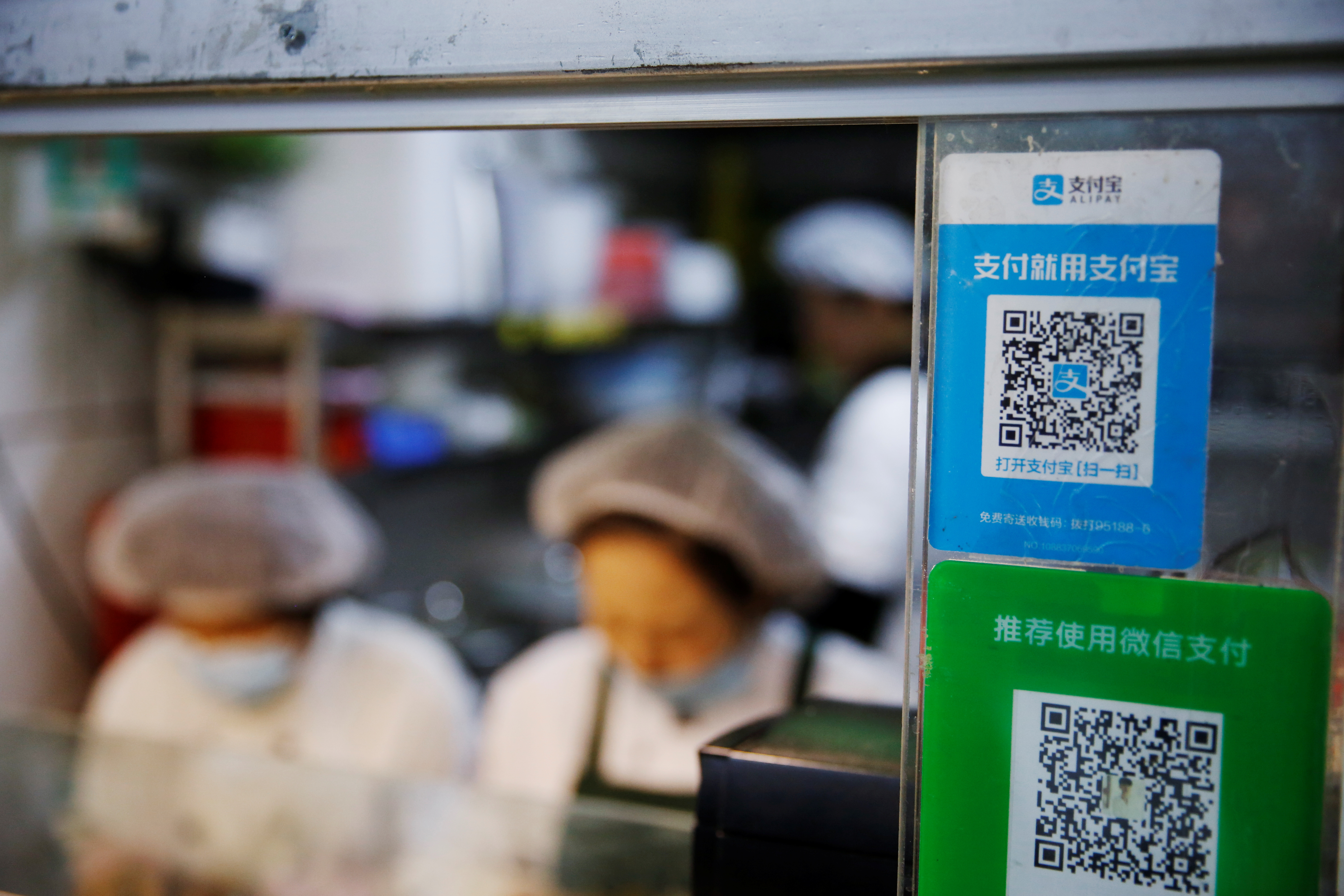 A QR code of digital payment device Alipay by Ant Group, an affiliate of Alibaba Group Holding, is seen next to a QR code of WeChat Pay at a food stall inside a market, in Beijing, China November 2, 2020. REUTERS/Tingshu Wang