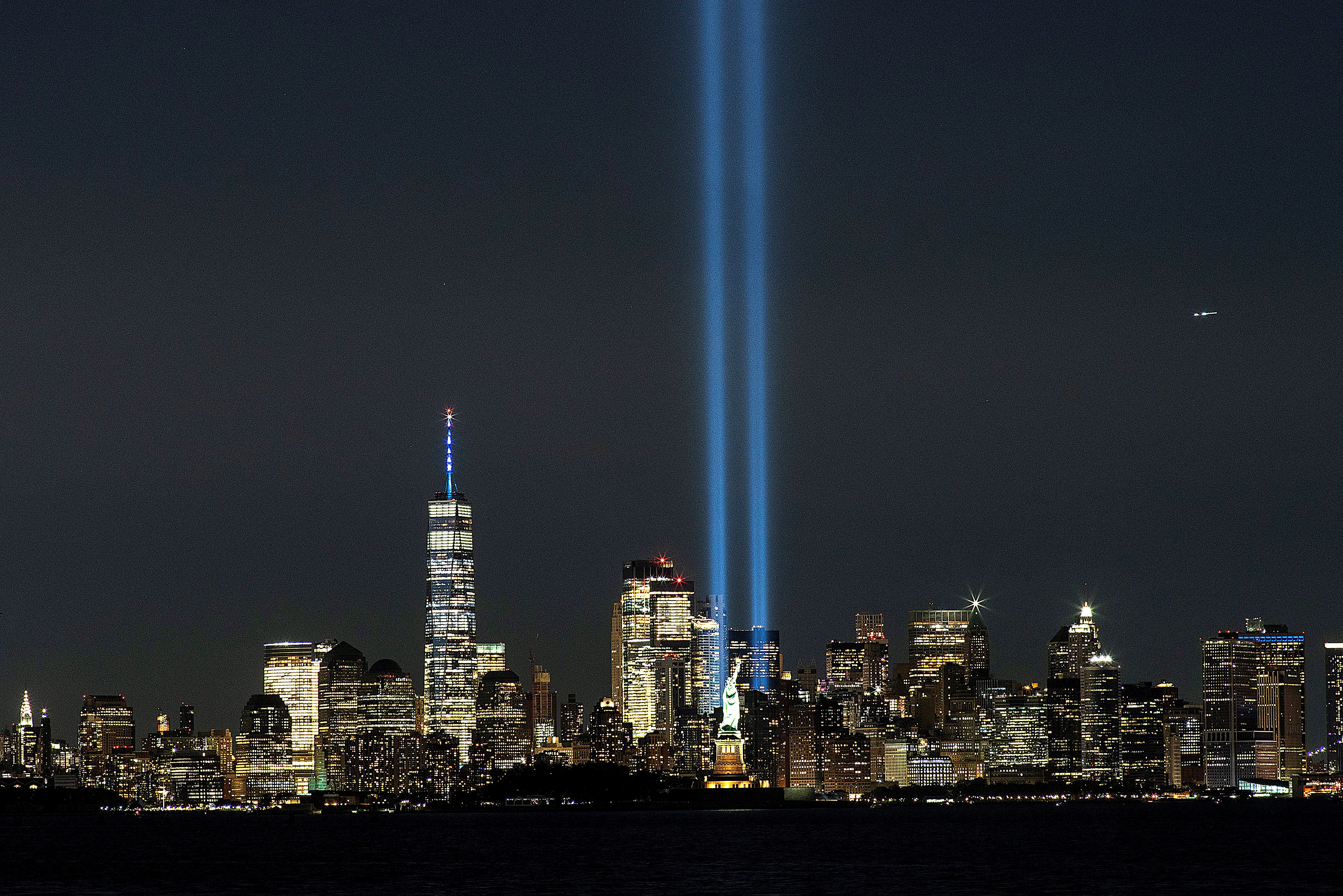 The Statue of Liberty and One World Trade Center are seen as the Tribute in Light shines in downtown Manhattan.