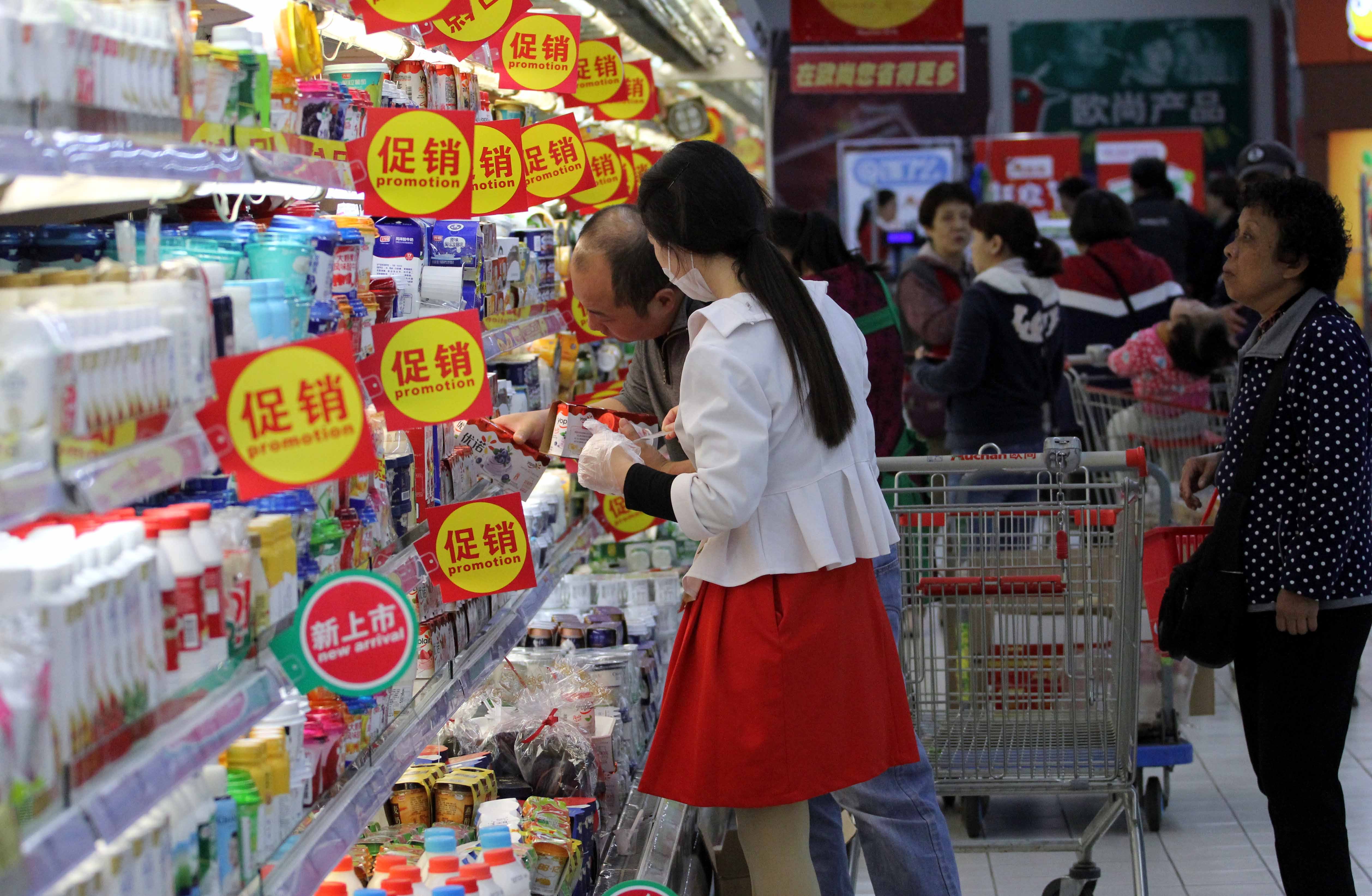 """--FILE--Customers shop for dairy products due to discounts at a supermarket in Nanjing city, east China's Jiangsu province, 16 October 2017.Consumers who are anticipating cheaper prices for products during the upcoming Nov 11 shopping festival may not necessarily find them online, a new study said. According to the 2017 China shopping report jointly released by market consultancies Bain & Co and Kantar Worldpanel, the online prices of many product categories are higher than those offered in physical stores, with the biggest price differences seen for toothbrushes, hair conditioners and kitchen cleansing supplies. Jason Yu, general manager of Kantar Worldpanel for Greater China, said the price differences can be largely attributed to the fact that relatively more high-end products are purchased online. """"While Chinese consumers used to shop online for low prices in the past, it has been increasingly noticeable in the recent five years that people prefer products that indicate a better lifestyle or entail more added value,"""" he said. As a result, the sales of imported goods, especially food products and personal care products, have risen significantly, he said. """"To cater to this trend, leading e-commerce players such as Alibaba and JD.com have upgraded their offerings on their platforms to meet the demand of the rising middle class and younger consumers,"""" he said.No Use China. No Use France."""