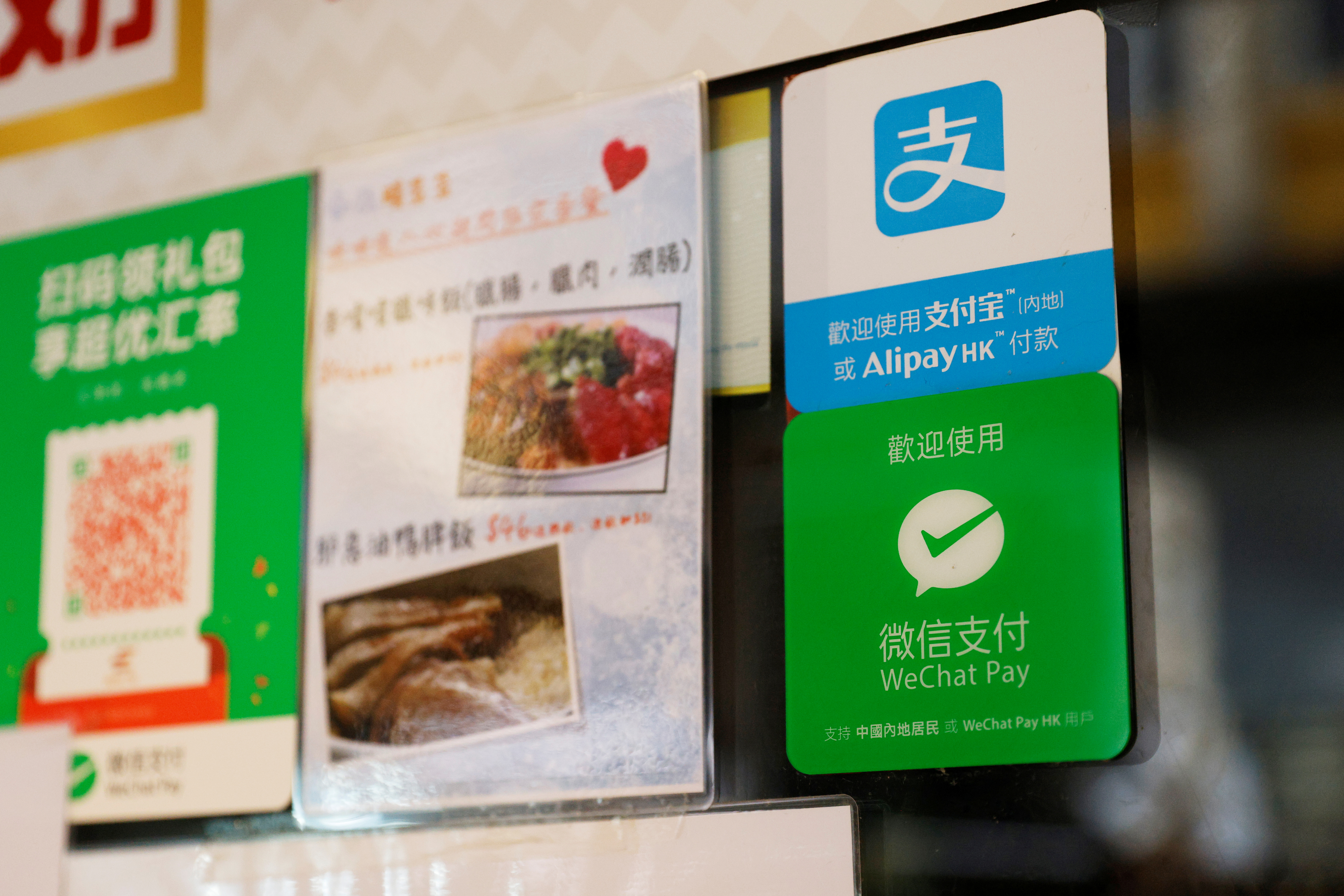 Logos for digital payment services Alipay by Ant Group, an affiliate of Alibaba Group Holding and WeChat Pay by Tencent Holdings are displayed outside a restaurant, in Hong Kong, China November 1, 2020. REUTERS/Tyrone Siu