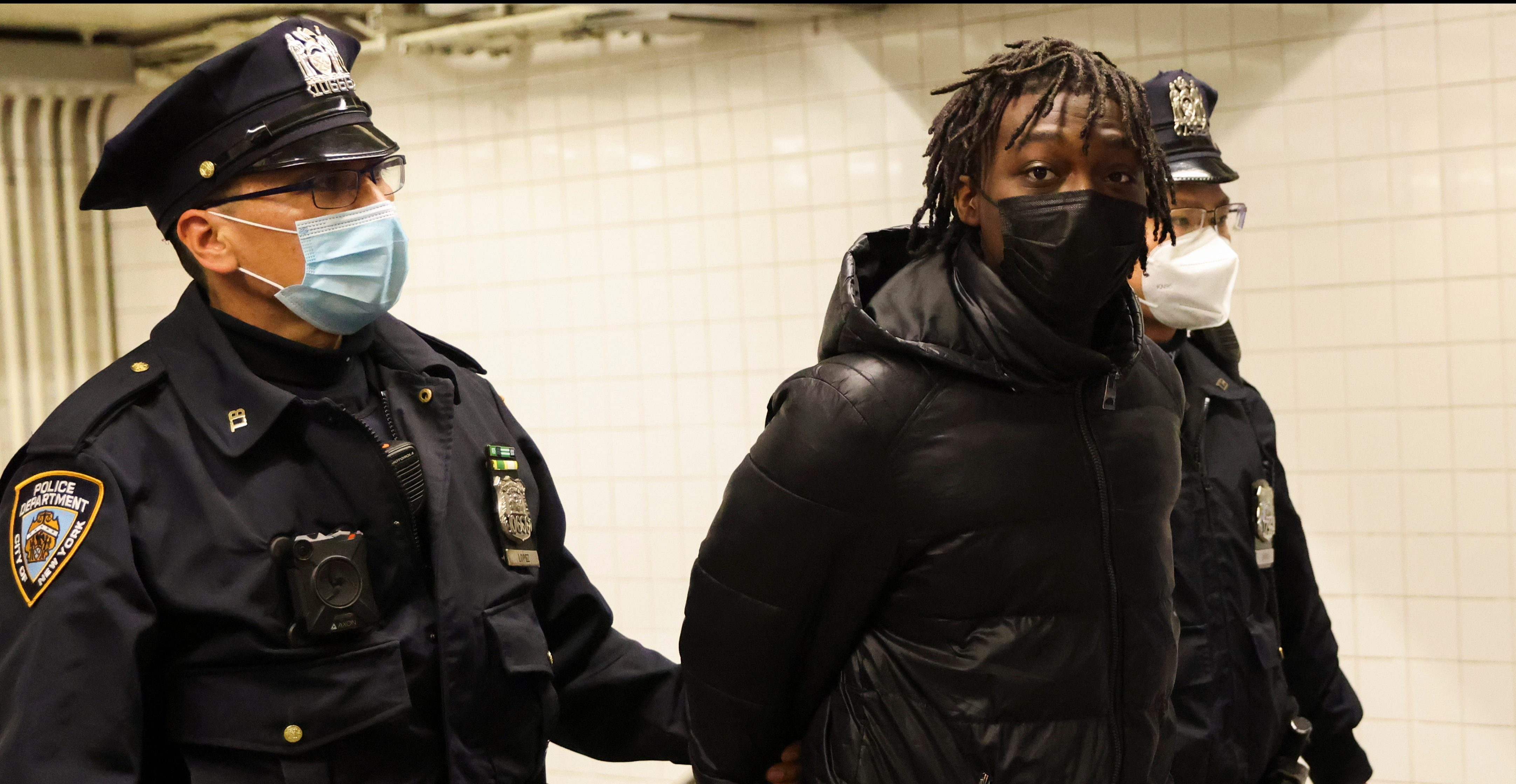 New York City Police Officers (NYPD) transport Saadiq Teague, 18, from the Columbus Circle Transit Bureau Police Station, where he was charged with two counts of criminal possession of a weapon second degree, two counts of criminal possession of a weapon in third degree; one count for the assault rifle and one for ammunition, and no one count of criminal use of drug paraphernalia after being found with an unloaded semi-automatic gun, ammunition and a gas mask outside a Times Square subway station, in New York City, U.S., April 16, 2021. REUTERS/Caitlin Ochs