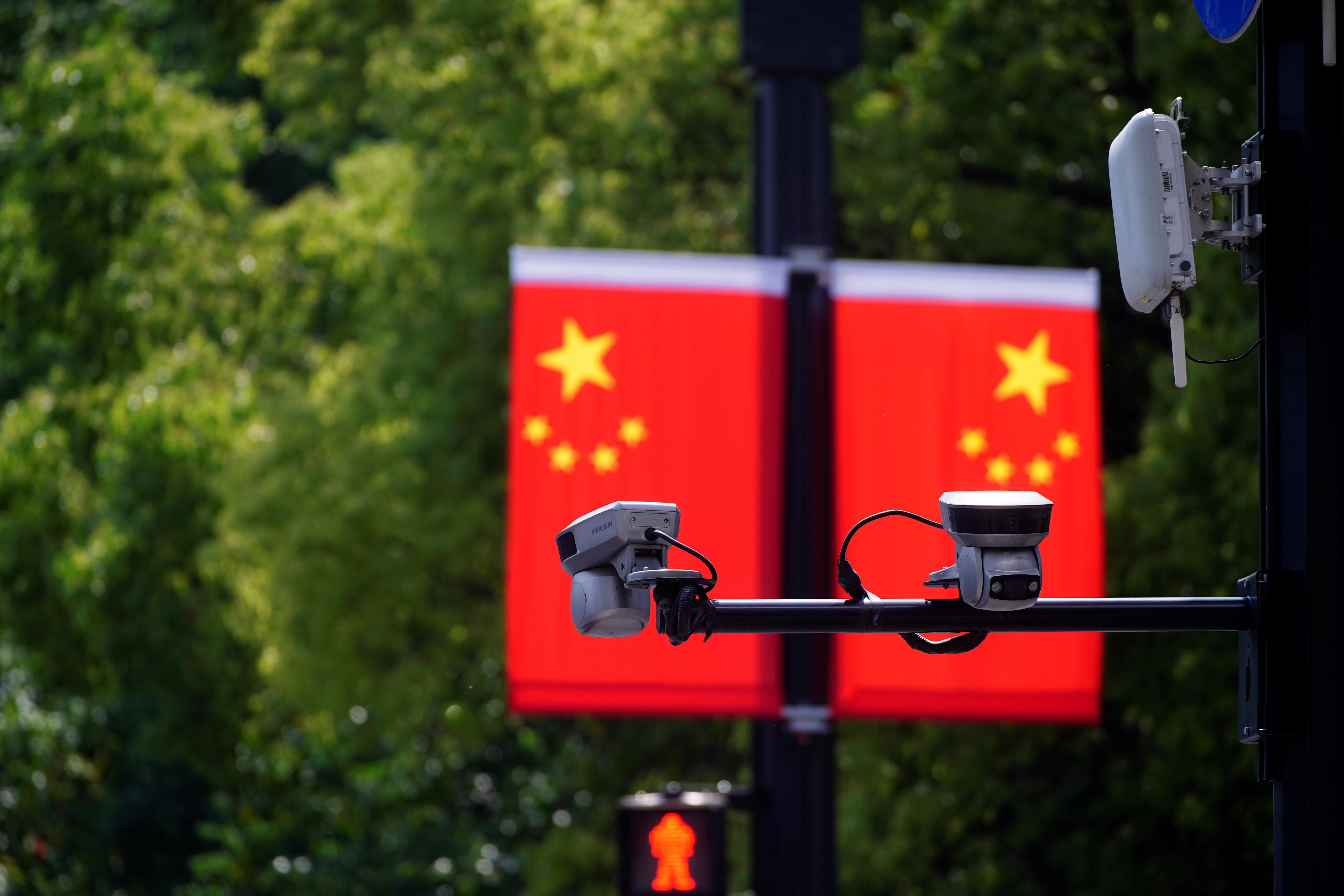 Hikvision surveillance cameras are seen in front of a Chinese flag at a main shopping area, during the Labour Day holiday, following the outbreak of the coronavirus disease (COVID-19), in Shanghai, China May 5, 2021. REUTERS/Aly Song