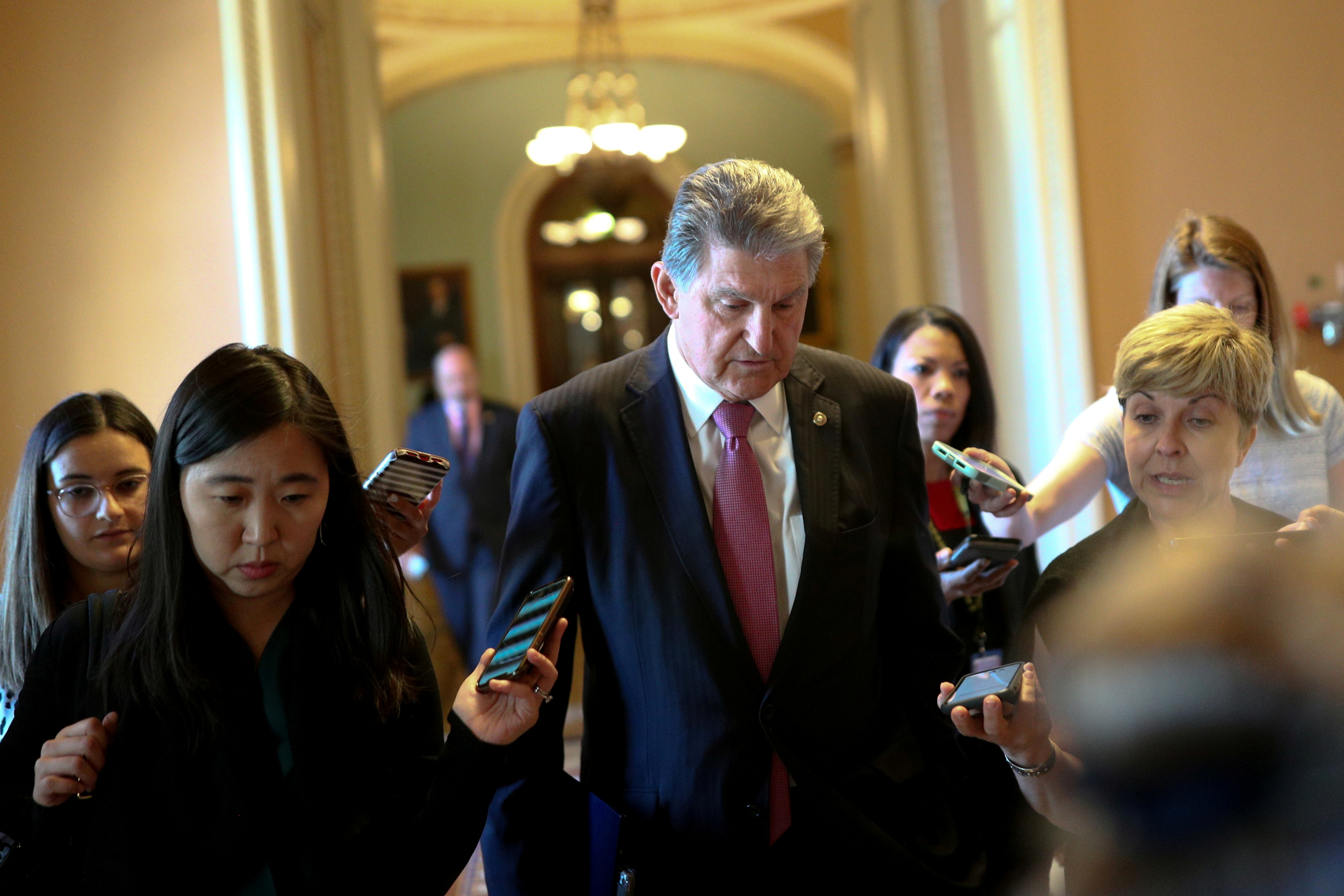 FILE PHOTO: Senator Joe Manchin (D-WV) speaks to news reporters before attending a meeting on infrastructure on Capitol Hill in Washington, U.S., June 23, 2021.  REUTERS/Tom Brenner/File Photo