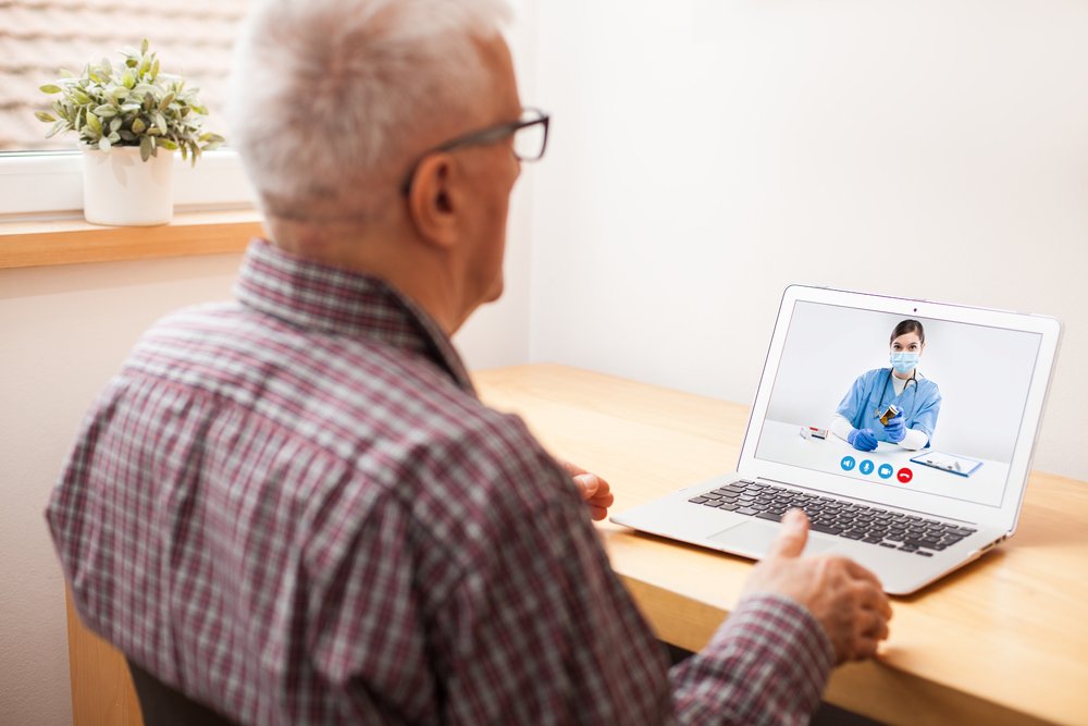 Young e-doctor consulting elderly man,online video help line virtual medical appointment,GP prescribing medication to senior patient,telemedicine diagnosis,tele visit remote health concept