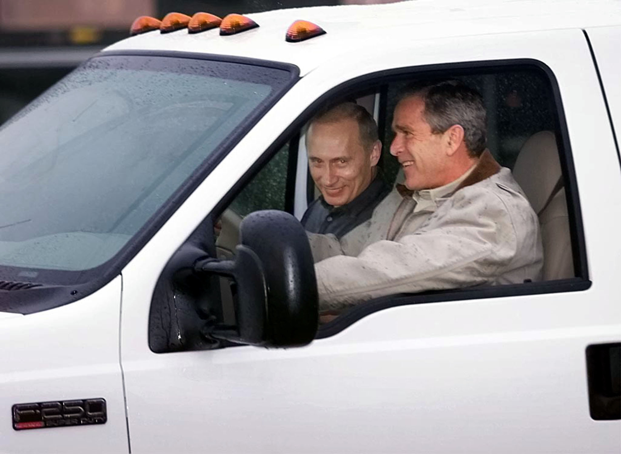 U.S. President George W. Bush rides with Russian President Vladimir Putin in the front of his pickup truck as he welcomes Putin to his ranch in Crawford, Texas November 14, 2001. [Bush plans to treat Putin to Western-style entertainment and tour of his beloved ranch, as well as follow up on their talks in Washington on Tuesday on a new strategic relationship. ] Win McNamee / Reuters.
