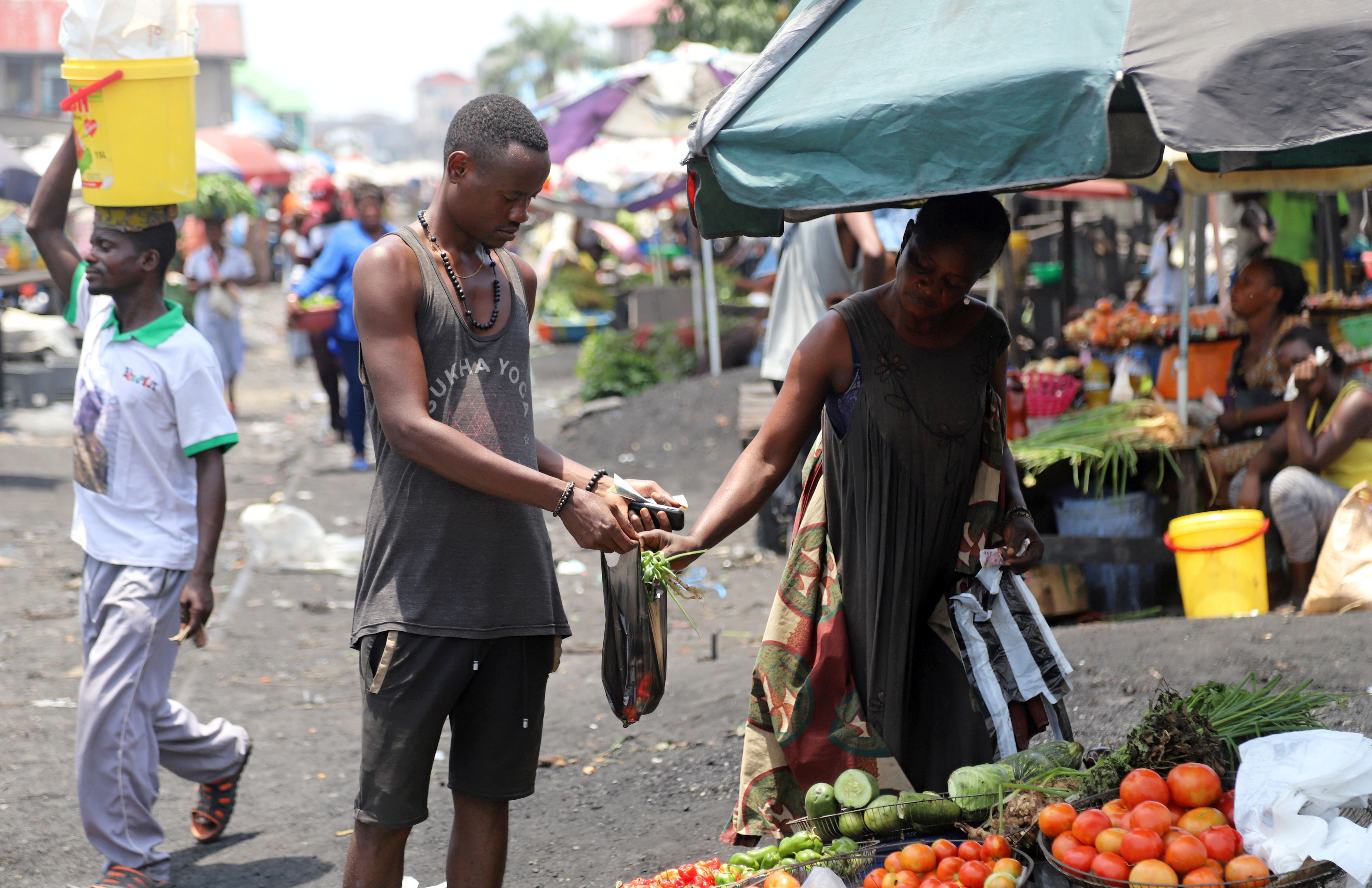 FILE PHOTO: A Congolese man buys groceries at an open air market, amid concerns about the spread of coronavirus disease (COVID-19) in Kinshasa, Democratic Republic of Congo, March 28, 2020. REUTERS/Kenny Katombe/File Photo