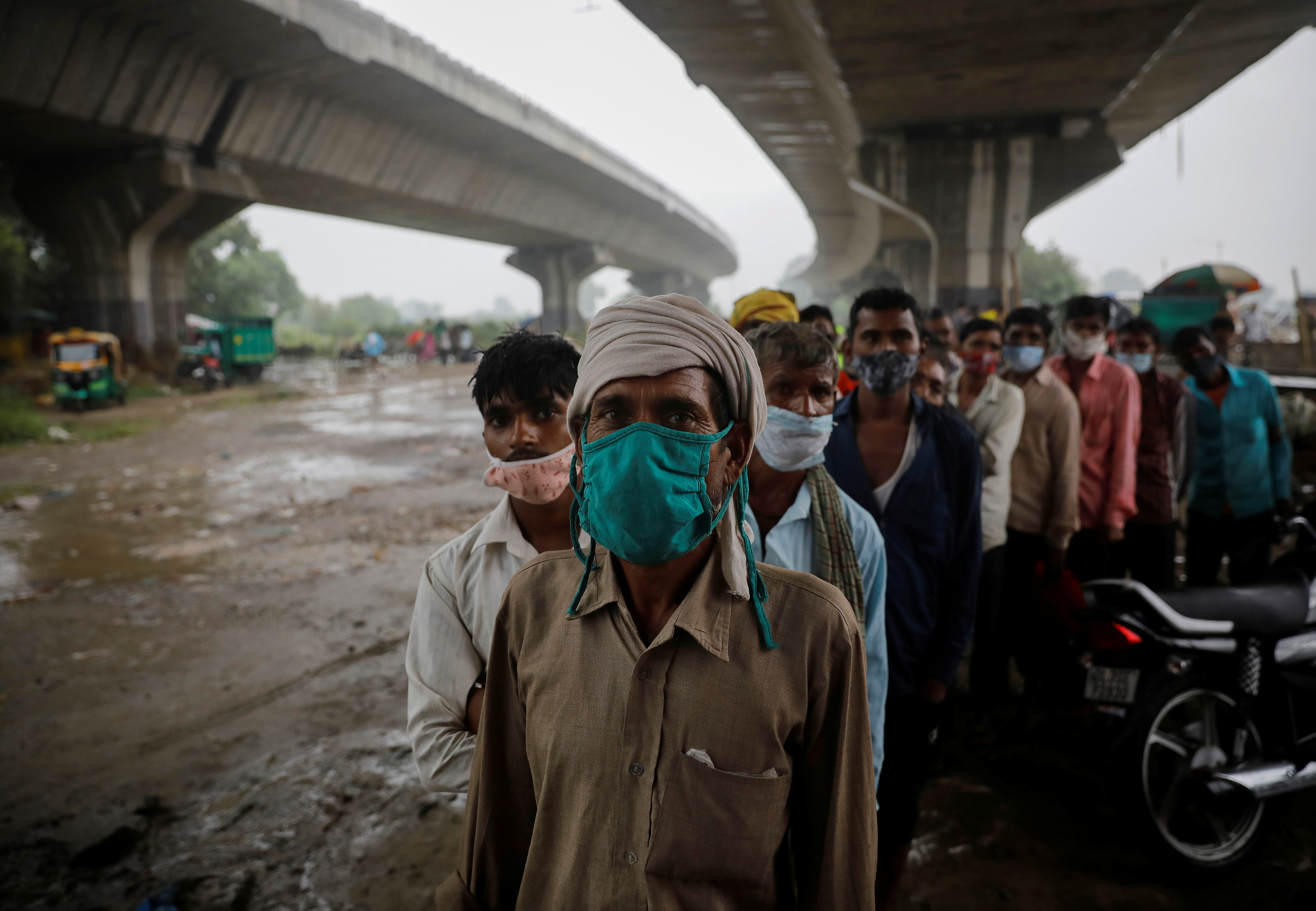 People wait to receive a dose of COVAXIN coronavirus disease (COVID-19) vaccine manufactured by Bharat Biotech, during a vaccination drive organised by SEEDS, an NGO which normally specialise in providing relief after floods and other natural disasters, at an under-construction flyover in New Delhi, India, August 31, 2021. REUTERS/Adnan Abidi