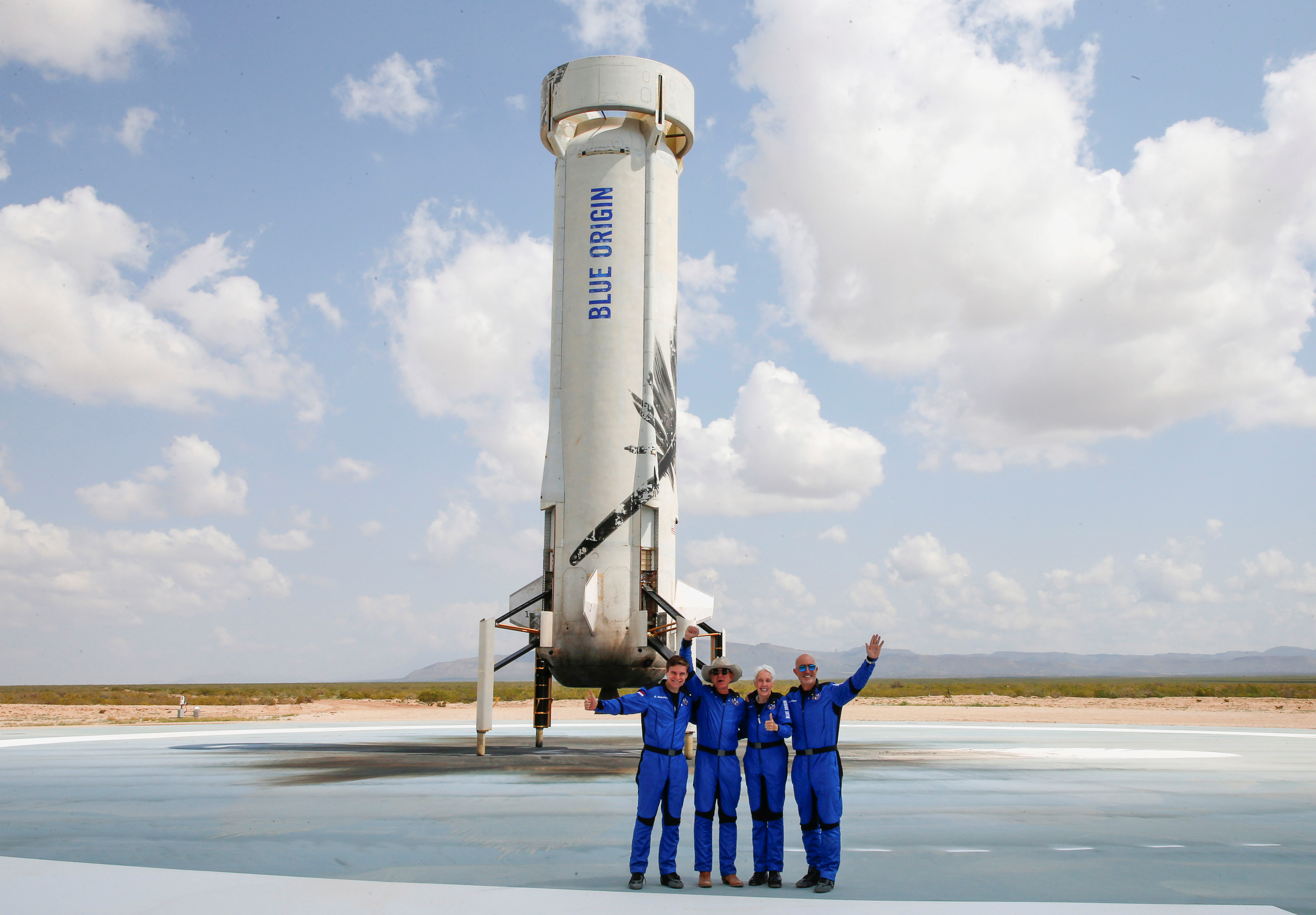 Billionaire American businessman Jeff Bezos (2nd-L) poses for pictures with crew mates, from left, Oliver Damen, 18, Bezos, Wally Funk, 82, and Mark Bezos at the landing pad after they flew on Blue Origin's inaugural flight to the edge of space, in the nearby town of Van Horn, Texas, U.S. July 20, 2021.   REUTERS/Joe Skipper