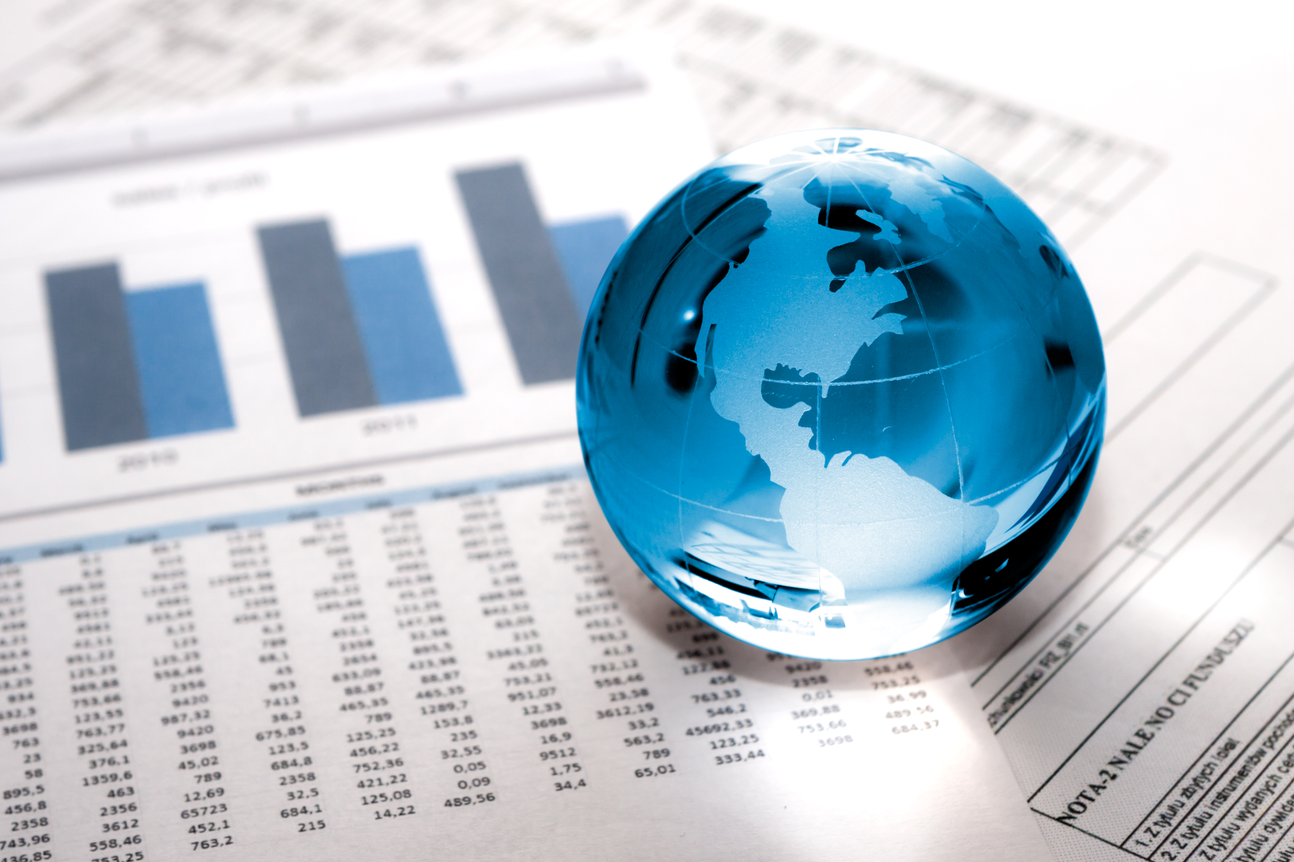 Glass globe on top of business papers