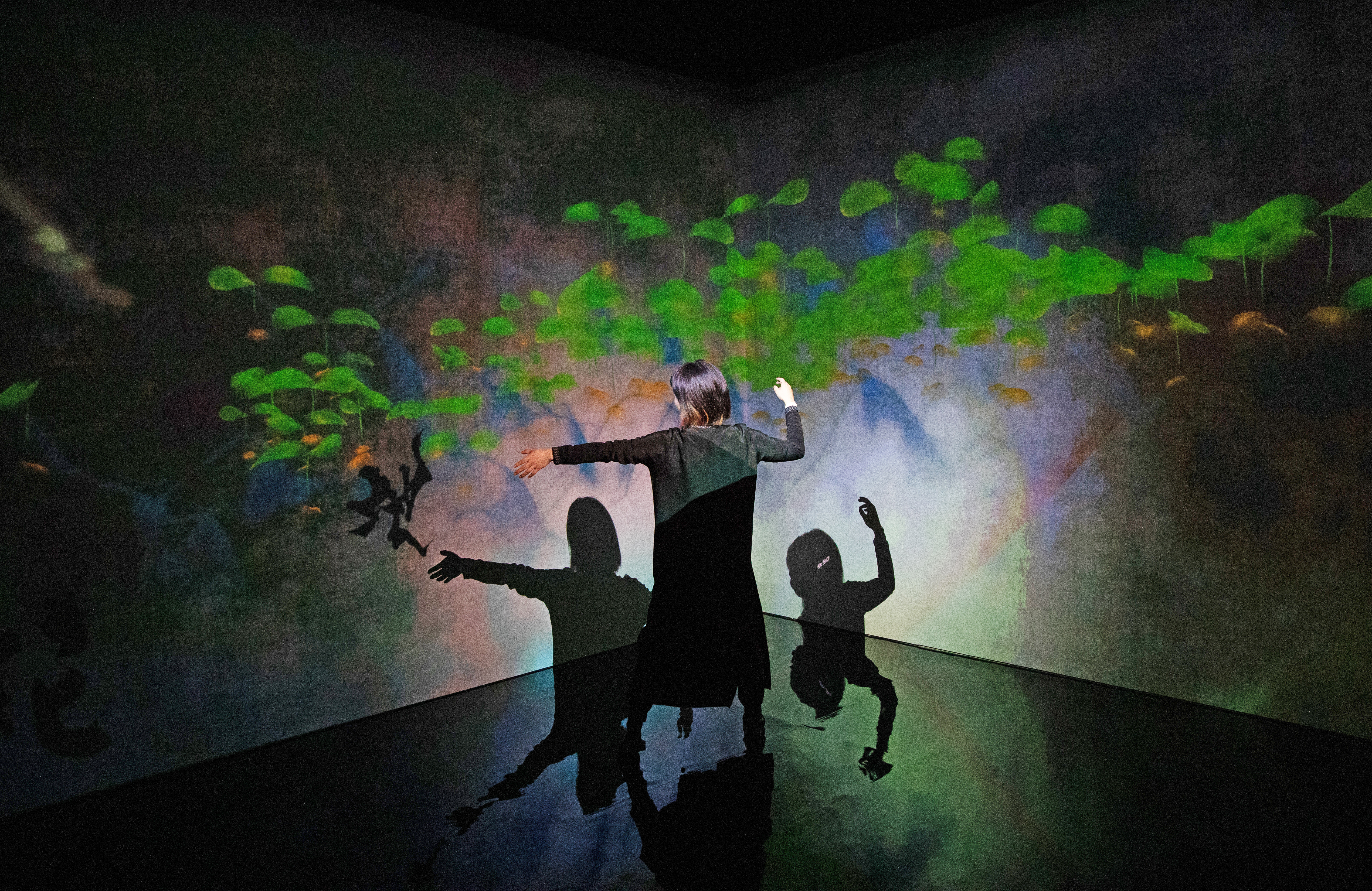 A woman interacts with a digital art installation exploring the relationship between humans and artificial intelligence.