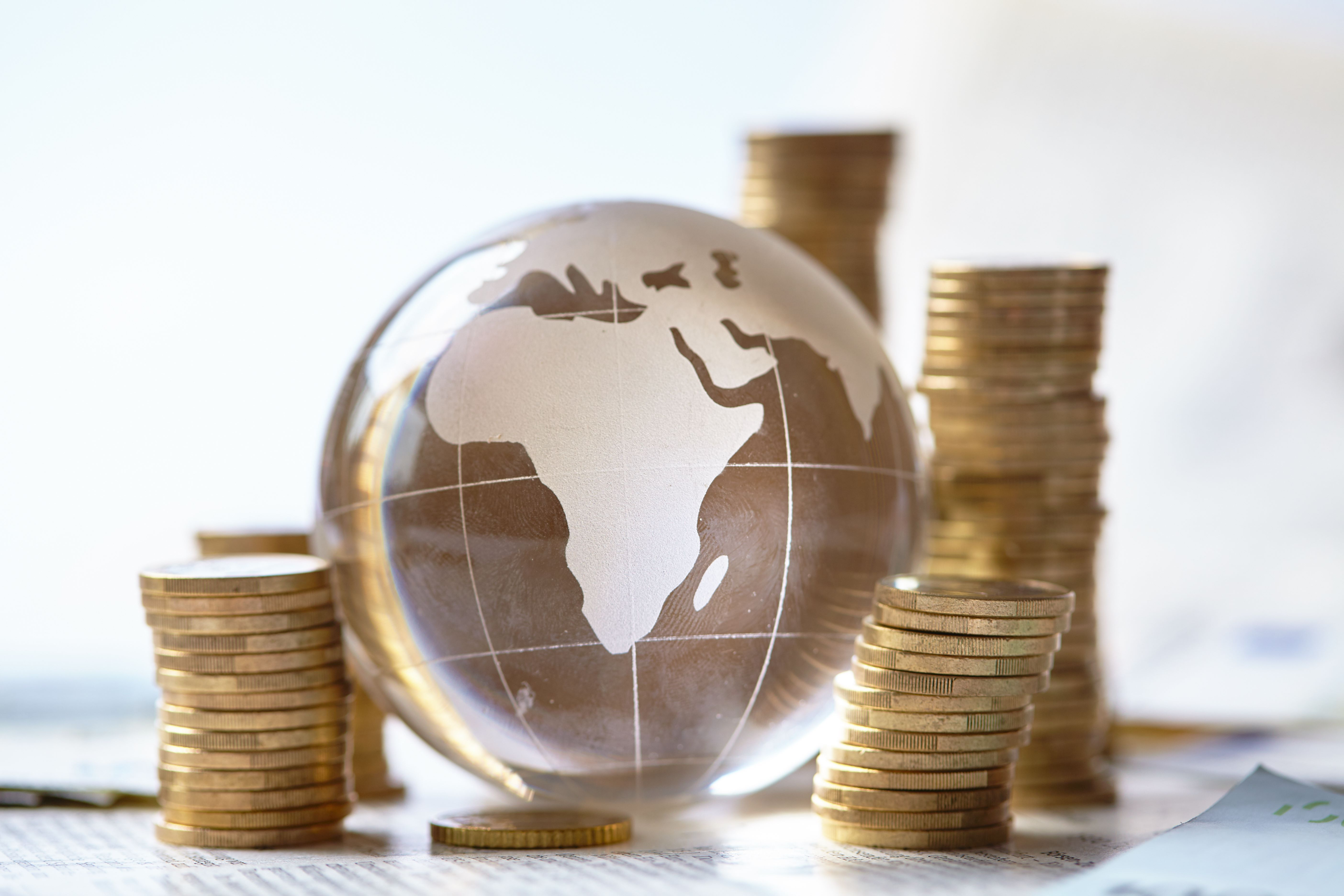 Coins piled around a globe featuring Africa