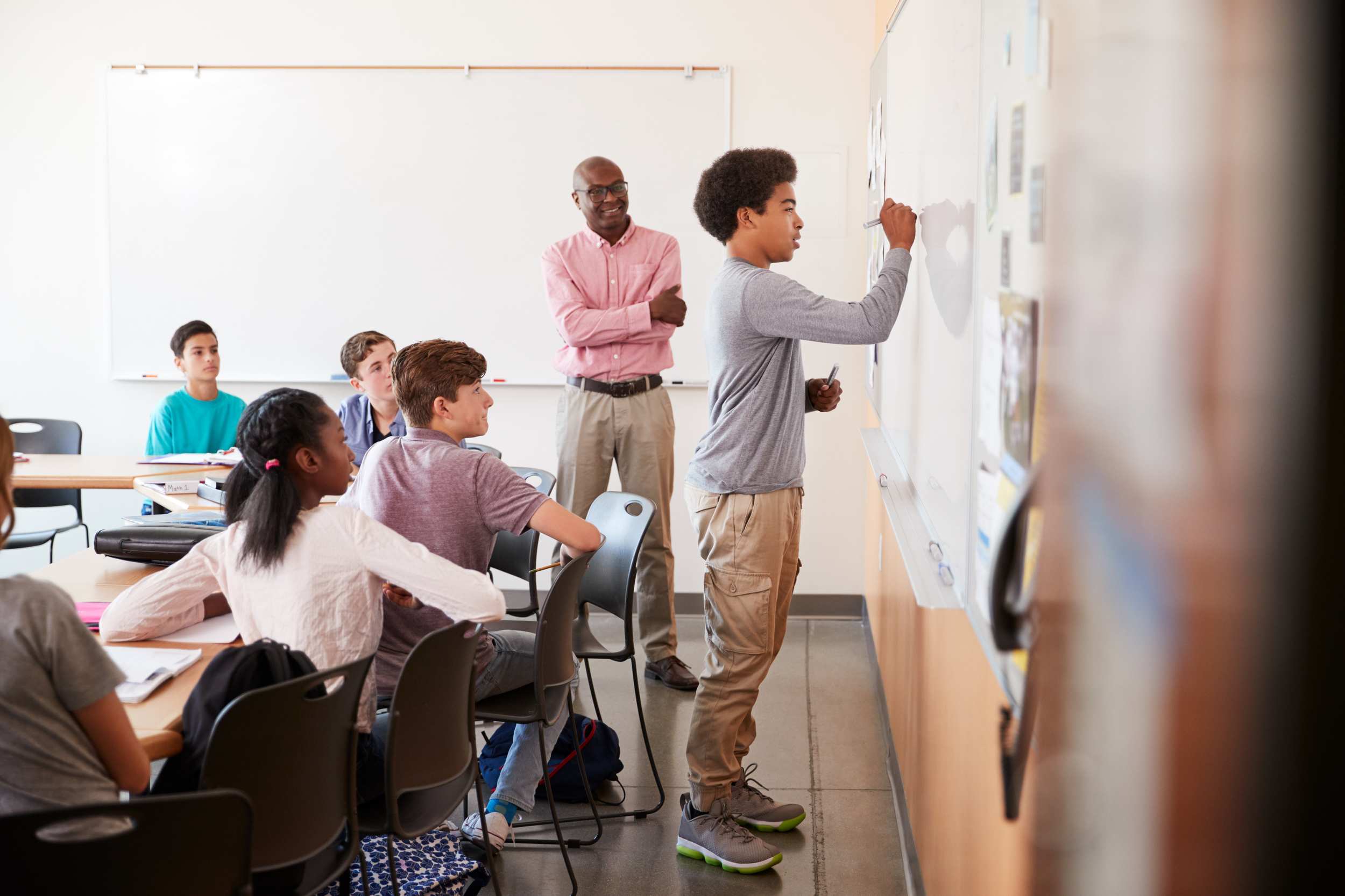 student at whiteboard in classroom
